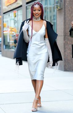 Keke Palmer in a white slip dress,s black coat and choker