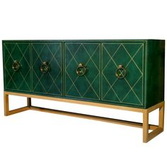 Tommi Parzinger Leather Credenza with Brass Handles  USA  c. 1950s  A rare Tommi Parzinger cabinet for Charak Modern c. 1950s. Completely covered in deep green leather, with gold details, amazing round brass door knocker pulls, sits and connected to a light original finish wood frame. So elegant and classic. Features two drawers and two shelves inside. Labeled Tommi Parzinger.