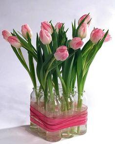 Nine glass bottles bound by ribbon form lovely flower vase/arrangement