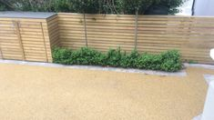 Resin bonded driveway with granite cobble edging, horizontal cladding bin storage and fencing in Balham.