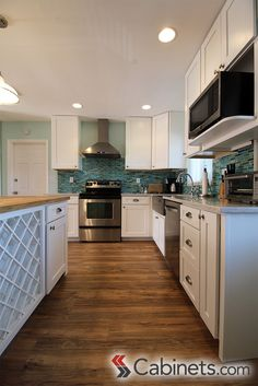 White coastal kitchen featuring Shaker style cabinets on the perimeter and island. #shakerkitchen