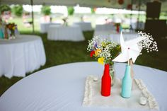 love the colored bottles, pinwheel and a little baby's breath with maybe some yarn pompoms cute