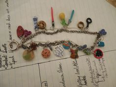 """Fandom charm bracelet! Right to left top to bottom it's Captain Jack's head scarf, Merlin sign, Ravenclaw tie, Greek Omega sign, lightsaber, pineapple (psych), Sting, the Ring of Power, Sherlock's spying glass, Teen Wolf sign, MATCHED cover symbol, """"Mahogany"""" table, Supernatural pie, DIVERGENT needle, New Who catchphrases, blue pancakes, Hogwarts crest, bow tie, Griever, Chuck Nerd Herd sign, River's Diary. I wanted to do so many more! If you want something similar, we can definitely discuss…"""