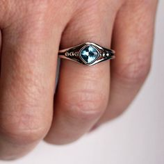 A unique gemstone ring that I hand fabricated with an organic feel and set a cushion shaped blue topaz in the center. Then I oxidized and gently