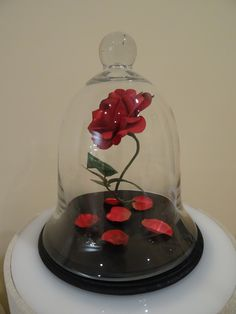 Beauty & the Beast Rose centerpiece for sweet 16 (DIY). glued rose with fishing line to inside of glass dome.