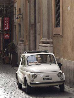 Fiat 500 car parked next to Roman building