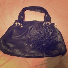 Black flower handbag EUC black handbag with flower detail. Has 3 compartments. Very spacious bag. Only flaw is that 1 inside compartment is ripped other than that it's in excellent condition. Used only a handful of times. Bags Shoulder Bags