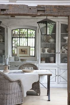 Kitchen white-washed cabs with diamond shape on cabinet door, chicken wire insert, rattan chairs, rustic table