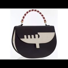 Moschino Black & White Leather Venice Bag With the inspiration of one of Italy's most famous and beautiful cities, and by one of the most stylishly Italian names, this bag is the perfect accessory to add to a look for a fun take on a classic style. Done in black leather, featuring a white leather silhouette of a canal boat, this bag is effortlessly chic. Featuring red and white rolled leather handle, gold tone hardware, hook clasp closure, black canvas and one zip pocket. This bag is in very…
