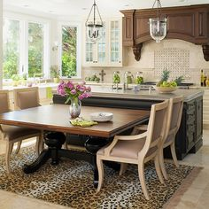 A stunning pewter-topped island is the centerpiece of this French-inspired kitchen. The decorative edge on the countertop adds an unexpected twist to the black base. To add seating, the homeowner pushed a custom walnut table against the island. The elegant table adds dining room formality to this in-kitchen eating area.