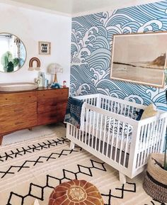 This beachy kids bedroom is complete with an ocean wave wallpaper, alongside adorable woven furniture and wooden accent pieces. This surfer girls bedroom idea is perfect for a surfer themed bedroom wall. surfer girls bedroom, gender neutral nursery wallpaper, beach room decor, surfer kids bedroom wall, surfer room decor. #surfergirlbedroom #beachhousedecor #beachroomdecor