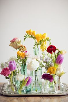 Instead of a bouquet, try placing blooms in an arrangement of smaller vases.