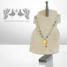 Collar elaborado con turquesas ovaladas, dije en forma de pluma y moneda en bronce con baño en oro. http://www.elretirobogota.com/esp/?dt_portfolio=pequenas-indulgencias
