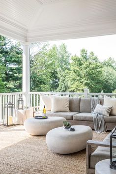 Modern covered patio features a low armless outdoor sofa lined with ivory pillows facing a pair of West Elm Pebble Coffee Tables atop a jute rug.