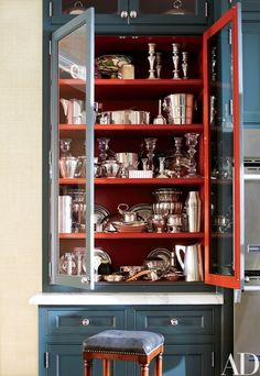 The interior of a kitchen cabinet echoes the red accents in the other ground-floor rooms, including the living room's seating and the library's throw pillows and rug | archdigest.com