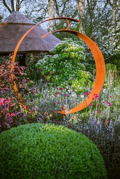 A wider view of the commemorative show garden. The curves of the sculpture, thatched hut, and box ball echo each other well.  Canon EOS 5D mark III, Canon EF 24-105mm f/4L IS USM. 55mm, f/4, 1/400, ISO 200.