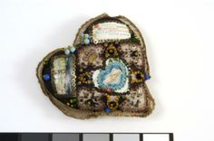 Heart-shaped pincushion in the Imperial War Museum collection, decorated with glass beads, sequins, decoupage of ship, above inscription and marriage handshake, and enamel crown; edged with ribbon. Applique: 'On this morning of your BIRTHDAY All my thoughts are turned to you, And I send my warmest greeting'