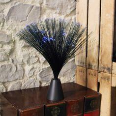 Bonita lámpara de fibra óptica de color azul, que al encender su luz, la traspasa por sus hilos de fibra óptica consiguiente un efecto relajante (luz en color blanco).