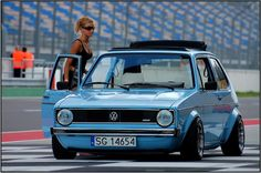 Girl and baby blue VW Golf
