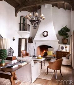 The living room's wood ceiling, wrought-iron chandelier, and fireplace are original to the house. The Swedish trestle table and the marble plaque of Virgil are 19th-century.