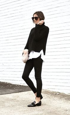 Black sweater over a white shirt and black pants