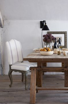 A casual, bohemian dining moment from Ralph Lauren Home's Ile Saint-Louis collection, where black enamel lighting meets  a worn oak table and a graceful rococo dining chair in lilac striped linen