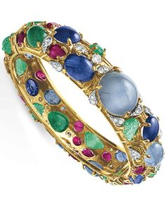 A DIAMOND AND MULTI-GEM BANGLE BRACELET  Designed as a hinged gold bangle, centering upon a cabochon star sapphire, set with a series of carved emerald leaves, variously-cut rubies, cabochon sapphires and emeralds, enhanced by circular-cut diamonds, mounted in gold, 6½ ins.