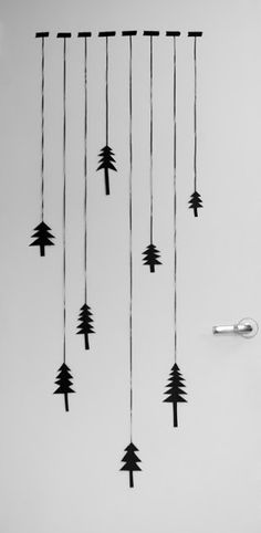 I like.....make or buy trees, suspend with ribbon, twine or string from curtain rod, dowel or branch. Then hang in window?