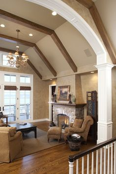 In the family room, on a less grand scale, this is what I'd like to do to the fireplace-- remove the two wall areas on the side, slope up the plaster around the fireplace, and have an all-around (or beamed) mantel.  Also, encase the current tiled fireplace with wood, brick, or stone.