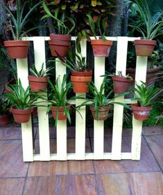 Re purpose! Painted pallet displaying Orchids in clay pots secured with hangapot hangers.