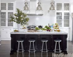 Black and white kitchen: The shimmering white backsplash paired with the white kitchen cabinets and black island really softens this look. Great use of silver in the lights and bar stools ties everything together.
