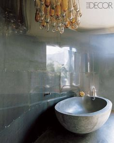 The dramatic egg-shaped concrete bathtub was custom-fitted to his body. The walls are sheathed in sheet metal, and the light fixture is from the 1950s.