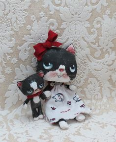 Black and white cat doll and kitten cloth dolls by suziehayward, $85.00 This sweet pair are sold together.Mama is aprox 7 inches tall with blue green eyes .Her dress is made from recycled cotton jersey pattered with lil cat heads and the word meow . Her baby is aprox 3 inches tall .Their arms are wired .Each doll is hand made and hand painted