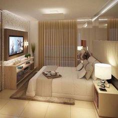 Quarto de casal neutro, mesa lateral com abajur, cortina creme, papel de parede, cabeceira com espelho.