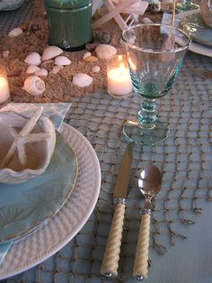The pale turquoise tablecloth is topped with a fishnet throw from Michaels. The flatware is from CTS looks like sand, and the stemware is from HomeGoods