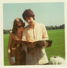 Candid photo of Paul signing Pepper LP for fan in park, as Martha his dog looks on,