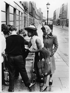 Two women talk to youngsters in Southam Street. The photos were all taken by Roger Mayne...