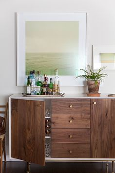 Zoe and Max transformed a midcentury console into a chic bar by placing a gold tray with various libations on top of it. The bar also doubles as storage for tumblers and drinking glasses when they aren't in use.