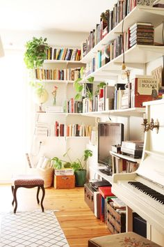 Piano, hanging shelves, trunks on the floor, and a light and bright space