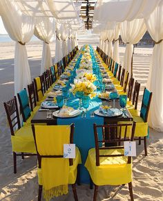 For this intimate beachside wedding, celebrity wedding planner, Mindy Weiss, played with two equally bold colors: blue on the tabletops with pops of yellow in the centerpieces and chair covers. She topped it off with a simple white draped fabric canopy