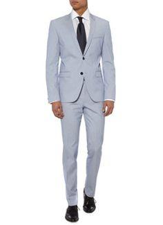 Adris3/Heibo3 slim fit kostuum van HUGO. Het zomerse pak is opgebouwd uit een fijne katoenblend en is uitgerust met verticale strepen in het wit en blauw. De set bestaat uit een single breasted-colbert met twee knopen. Deze komen ook in een kleinere variant als twee duo's kissing stacked buttons terug op het manchet. Verder is het jasje afgewerkt met een strookzak voor het pochet en een tweetal klepzakken. Bij het kostuum hoort een pantalon. Deze is uitgerust met een dubbele haak- en…