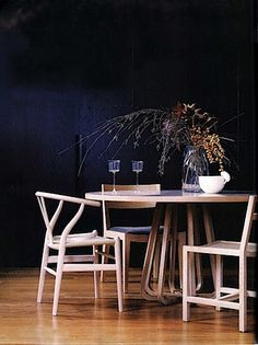 dark walls and wishbone chairs