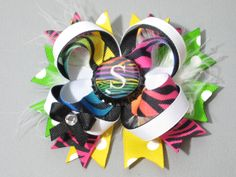 "Rainbow initial bottle cap hair bow. You can find my bows on Ebay. ""thehiddenloft"" or ""Lisa's Little Bows"". I also do custom made bows, so let me know if you would like a certain bow made."