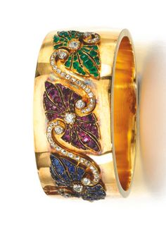 GOLD AND GEM SET BANGLE, LATE 19TH CENTURY The hinged bangle set to the front with a three part shield motif composed of cushion-shaped and single-cut diamonds and square- and oval-shaped rubies, emeralds and sapphires.