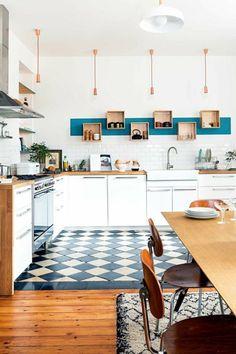 une cuisine rénovée ouverte sur le salon, plan de travail en bois naturel et des placards blancs