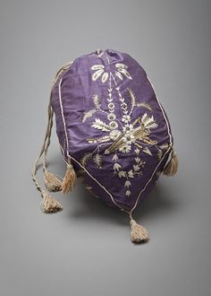 Reticule (Purse) 1810, French, Made of silk ~~~~~ The reticule bag was a new accessory in the late 1790s because before then, women had carried their pockets about their waist when their gowns had been large enough to hide them. The advent of slender columns of muslin meant that pocket purses could be seen beneath dresses and so the reticule came into fashion.