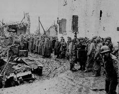 Soldats allemands capturés dans une zone d'attente dans les ruines de Junkersdorf (Allemagne), est gardée par les américains du 39e régiment d'infanterie, 9ème Division d'infanterie le 12 décembre 1944 Captured German soldiers in a holding area in the ruins of Junkersdorf, Germany, being guarded by Americans of the 39th Infantry Regiment, 9th Infantry Division on December 12, 1944