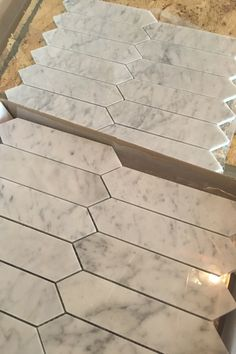 """Italian Bianco Carrara marble mosaic tiles available in 2""""x8"""" elongated hexagons pattern, 1"""" hexagons, 2"""" hexagons, 2"""" squares, mini brick herringbone, trellis pattern, chevron, arrow pattern with Antique Mirror accent, beveled diamonds, 1"""" penny rounds & elongated octagons with grey marble accent dots. Carrara marble displays a beautiful color variation of white and grey veins. Carrara marble bathroom tile 