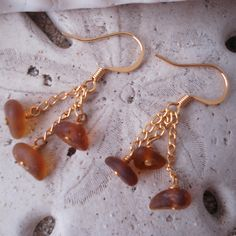 """Root beer brown sea glass dangle on 14kt gold filled wires with 14kt gold filled French hooks. Longest dangle about 7/8"""". These pretty earrings are delicate, light weight and easy to wear. The color of the sea glass goes with everything and you'll find yourself wearing these earrings all the time this summer.  Location - sea glass found on Southern California beach"""