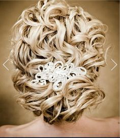 Naturally curly updo for wedding with hair pin.